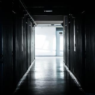 Ein dunkler Gang im Krankenhaus. Am Ende ist Licht zu sehen.